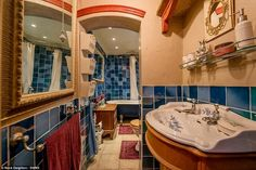 The bathroom of the house has been decorated with blue tiles and vintage style free-standi...
