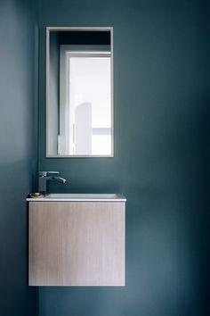 De hvitpigmenterte eikefrontene står i fin kontrast til den mørke fargen på gjestetoalettet.