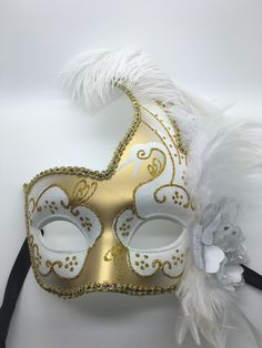 White and gold Mardi Gras mask with white feathers and ribbon ties.