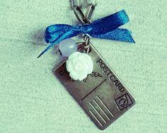 Collana vintage di bronzo antico con cartolina di bronzo, rosa bianca, piccola perla lilla e fiocco blu, fatta a mano, come da foto. La catena misura ca. 70 cm e indossata avrà una lunghezza di ca. 35 cm.