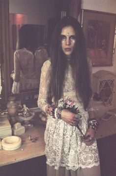 Swathes of old, discoloured lace, layers of beeds, armfuls of old fashioned blooms and a beautifully gem-adorned face.