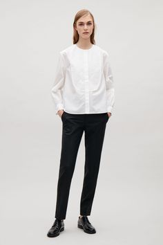 This shirt is made from pure cotton with a tactile, woven finish. A boxy fit, it has bib detail at the front, a simple, collarless neckline and long sleeves with gathered cuffs.
