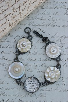 """she is her own best thing"" bracelet : resin, mother of pearl buttons, bezels, glitters."