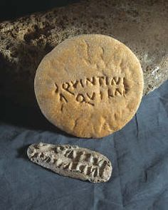This item comes from: Roman Legionary Museum (Item reference: 32.60). A leaden bread-stamp, reading 'Century of Quintinius Aquila'. Each century, of 80 men, baked its own bread, and sometimes marked it.