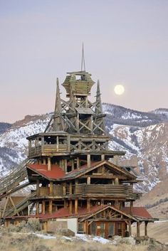 A full moon behind the five-story home of Francis Lee Smith, an engineer who labored on the house singlehandedly for more than a dozen years, in Wapiti Valley, Wyo., For nearly 30 years, Smith's home, now abandoned, has loomed over Buffalo Bill Cody Scenic Byway, and inspired many stories.