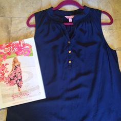 Lilly Pulitzer navy Houston Silk top This stunning pure silk navy sleeveless top features logo gold buttons. It looks great with any of your other Lilly pieces ( I wore it with white skinnies and gold shoes ). This is a size large, but I am a small and wore it as a loose tunic. It shows some signs of wear, mainly a very, very small hole(s) and water mark on the front. ( see pic, I put white paper beneath it to make it visible) I never noticed either while wearing bc I always wore a navy cami…