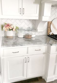 white kitchen with gray marble counter top and white subway tile back splash