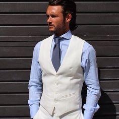 White pants, white waistcoat, blue dress shirt, blue polka tie