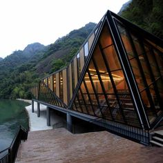 A triangulated glass and steel restaurant sits beside a river in a remote forested gorge in southern China