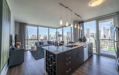 Modern, new luxury River North chicago apartment with floor to ceiling windows, hardwood floors, pendant lighting, and a kitchen island with wine storage