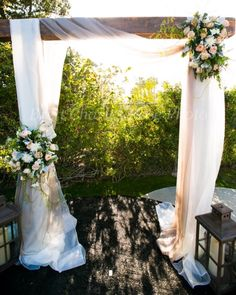 We created this wedding arch using pale gold and buff chiffon draping. Wedding sprays include white and peach English roses and seeded eucalyptus. Brett Charles Rose Photography.