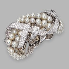 PLATINUM, CULTURED PEARL AND DIAMOND BANGLE-BRACELET, DAVID WEBB Designed as braided cultured pearl and diamond-set platinum strands, set with round and square-cut diamonds weighing approximately 25.00 carats, and cultured pearls, internal circumference 6½ inches, signed Webb.