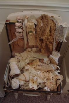 ~ Tarnished and tattered / lace and ribbons in an antique suitcase ~ (My grandmother's suitcase would be perfect for this)