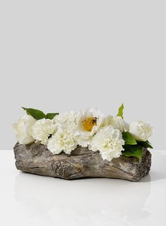 An arrangement of white carnations and peonies in a faux boix container.