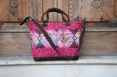 """This gorgeous traveling is in the hottest pink shades to make an amazing bag. Made from a Huipil, from a place called """"Nahuala"""" in Guatemala. Their traditional design features these diamond shape figures in various sizes and colors to make it one of a kind every time. Complemented with 100% Brown Guatemalan Suede Leather."""