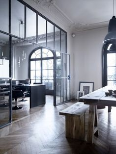 Vintage industrial office, black oversized windows, rustic seating + table, herringbone wood floors.