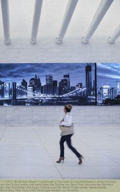 Frau läuft an Leuchtreklame in einem Korridor von the Oculus vorbei und sieht dabei die Skyline von New York, futuristischer Bahnhof des Star Architekten Santiago Calatrava bei der World Trade Center Gedenkstätte, Manhattan, New York, USA, Vereinigte Staaten von Amerika