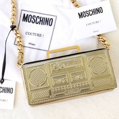 ♦️SALE♦️✨2x HP✨ Moschino 'Mini Boom Box' Purse This small, metallic leather Moschino clutch is beyond cute & ✨SOLD OUT✨ everywhere! DETAILS: Metallic front flap. Gold-tone chain strap. Lined interior. Leather: Calfskin. Weight: 9oz / 0.26kg. Made in Italy. Height: 3in / 7.5cm Length: 6.25in / 16cm Depth: 1.5in / 3.5cm Strap drop: 21.75in / 55cm ✨Few minor scratches inside, which is shown in photo #3 (purchased from store like that)- hardly noticeable. Comes with dust bag. ✨Retail Price…