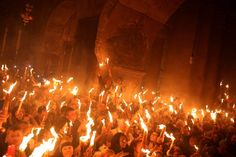 """Image: Christian Orthodox worshippers hold candles lit from the """"Holy Fire"""""""