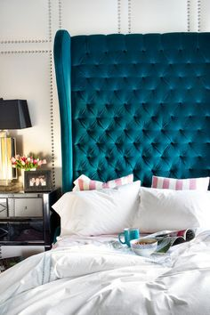 Upholstered walls. Bold color. Oversized velvet tufted wingback bed. Gorgeous!