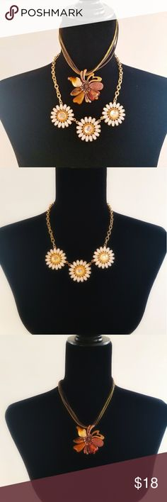 Two Enamel & Rhinestone Necklaces, Daisy Flower Two beautiful and whimsical pieces. The cheerful daisy necklace shines with white & yellow cut stones and a goldtone chain. The enamel and brass flower necklace glows with copper and cream hues, and is suspended from a woven ribbon cord. These items are preowned. Jewelry Necklaces