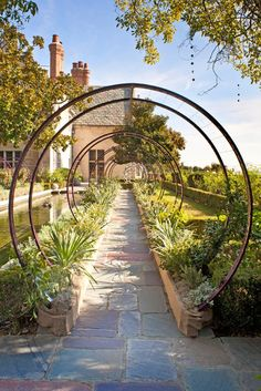 trellis could be made easily with recycled materials. Love the shape and position framing building and long walkway.