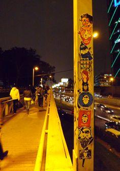 Pegar stickers  cerca de la estacion de Metropolitano de la Avenida Javier Prado. Las personas caminando con rapidez, otros caminando con cautela viéndome pegar stickers.