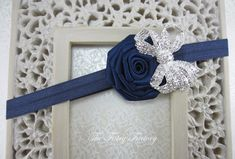 This fabulous headband consists of a 2.5 navy blue satin rolled rose embellished with a large sparkling rhinestone bow (the sparkle is