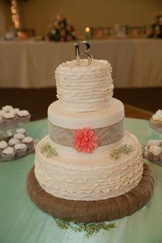 Country Chic wedding cake, with orange floral and burlap ribbon in classic ivory - Copyright: Bello Romance Photography