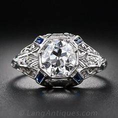 .97 Carat Early Art Deco Diamond Engagement Ring. A bright and lively European-cut diamond, weighing one carat, shines loud and proud from atop this beautiful, original vintage engagement ring, crafted in platinum - circa 1920. The magnificently ornamented ring is adorned all around with delicately pierced neoclassical design motifs punctuated by a calibre-cut sapphire at each corner. A teeny-tiny round sparkler twinkles from each shoulder