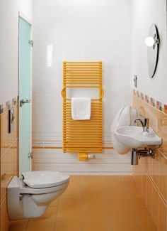 A fresh accent in a small bathroom is set by the by the bathroom radiator Ovida of the Villeroy & Boch by Zehnder-series in a retro-style orange. By the interplay of the matching tiles, the radiator more width to the room.