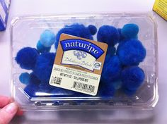 Blue pom poms as blueberries in a recycled container
