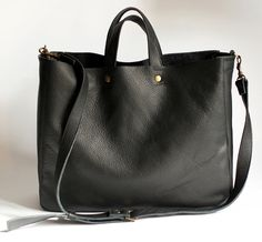 A large minimal bag on shoulder and hand. Made of black genuine leather. Inside without lining. Dimensions: Height 32 cm (12,6 ), width 38 cm (15), depth about 11 cm (4,3), strap detach, length approximately of 130 cm (51). Fits A4 and more. Close with two magnetic snaps, detal accessories in the color of old gold. For these bag, please expect 1 week for your item to be made and prepared for shipment!  Standard delivery time:  European union: 4 - 10 days  Europe (not EU): 7 - 14 days…