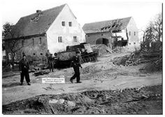 """Staff officers of the 1st Panzer Parachute First Division """"Hermann Goering"""" inspect the battlefield on the outskirts of the German city of Bautzen.  From heavily damaged buildings can be seen how serious were fighting for the city. April 26, 1945. Amongst the destroyed buildings lies a  self-propelled gun ISU-122 Soviet-made with a Polish eagle on the armor.  Behind the self-propelled gun is the body of a dead crew member."""