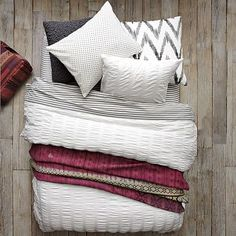 Layered looks plus pops of color on a white duvet = luxurious