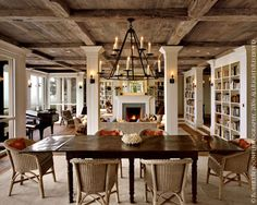 love all the contrasts...wicker, dark table, white columns, wood beams..and a shiny black baby grand....so eclectic yet soothing...