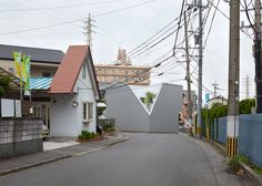 The corner appears to have been chopped off this house in Japanese city Oita, revealing a tree growing behind the building's walls