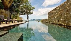Villa: Design Ocean Villa Infinity Pool And Modern Pool Lounge Chairs And Wooden Deck Natural Stone Wall Villa View Ocean In Thailand:  Samujana Holiday Villa - Exotic Holiday Villa in Thailand Built Around Natural Rock Formations