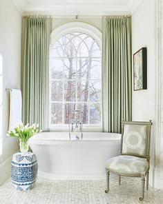 Elegant bathroom features a gray French chair placed before a roll top bathtub and a vintage hand held tub filler which stands under a palladian window dressed in green Greek key curtains.