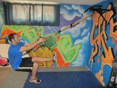 Single Leg Squats (sentadillas a una pierna) con TRX. Situarse de vertical, de cara al anclaje y sostener las cintas del TRX con ambas manos. Leventar una pierna. Descender flexionando la rodilla de la pierna de apoyo hasta que el muslo esté paralelo al suelo. Recuperar la posición inicial