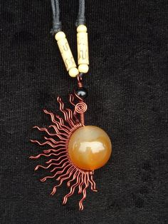 """Carnelian Obsialian Copper Wire Wrap Neckalce."" $40. Copper half sun around Carnelian stone with three wooden beads on each side of the necklace. Copper half sund and carnelian stone has the width and length of 2"" by 3"" with the black leather cord 10"" in length."