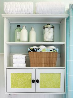 Adding scrapbook paper to glass doors is an inexpensive way to update a cabinet. Find more budget bathroom makeovers: http://www.bhg.com/bathroom/remodeling/makeover/budget-bathroom-makeovers/?socsrc=bhgpin062712#page=5