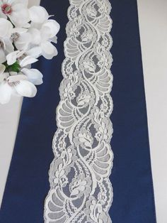 White lace as runner on blue ribbon, for a table decoration.