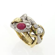 An Antique platinum and 18 karat gold ring with diamonds, star ruby and demantoid garnets. The ring has a rose-cut diamond with an approximate total weight of .85 carats, 9 old European-cut diamonds with an approximate total weight of .26 carats, a star ruby with an approximate total weight of .80 carats, and 2 demantoid garnet forming the eyes of the gold snake.  Available exclusively at Macklowe Gallery.