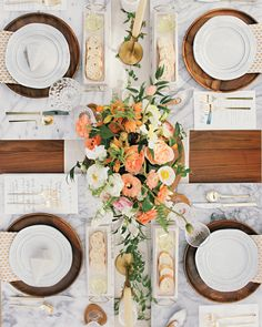 When you think of orange, perhaps a fall foliage color scheme comes to mind. But, by using bright hues paired with white or other electric colors, shades of orange make for a perfect summertime color palette.      For their intimiate vow renewal, this couple set an arrangement of orange-hued flowers from Studio Mondine onto the center of their dining table.