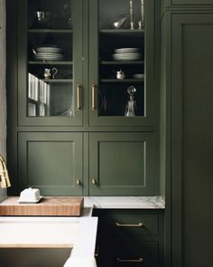 Glass front cabinets + green kitchen cabinets + eden green paint + stoffer home + brass drawer pulls and knobs + chunky cutting board + white marble countertops Classic Kitchen Cabinets, Shaker Kitchen Cabinets, Glass Front Cabinets, Green Cabinets, Kitchen Cabinet Colors, Kitchen Paint, Soapstone Kitchen, Kitchen Cupboard, Kitchen Cleaning
