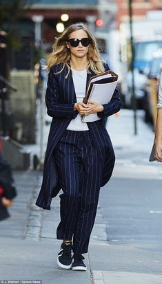 Ready for action: The 23-year-old Burberry model was clutching what appeared to be a script under one arm as she marched down the street