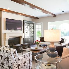 Dodson and Daughter Interior Design - living rooms - gray gourd lamp, gray double gourd lamp, bengal bazaar, flatscreen tv, tv over fireplace, wood beams, living room wood beams, nickel and glass end table, industrial coffee table, Kelly Wearstler Bengal Bazaar Graphite Fabric,
