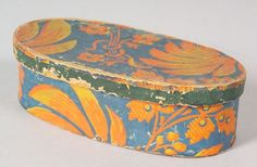 "Small Wallpaper Covered Bandbox, Berks County, Pennsylvania, second quarter 19th century, oval box with pine bottom, covered in orange and yellow flowers and leaves on a blue ground, the cover with a green rim band, the interior cover inscribed ""Miss Sally R. Stupp Host Berks Co., Pa.,"" ht. 2 dia. 6 7/8 in."
