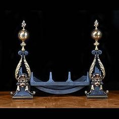 Antique pair of bronze mounted cast iron fire dogs in the 18th century style of open lyre form with leaf mounts, spherical and flame finials, on flared and rectangular bases. French 19th century.